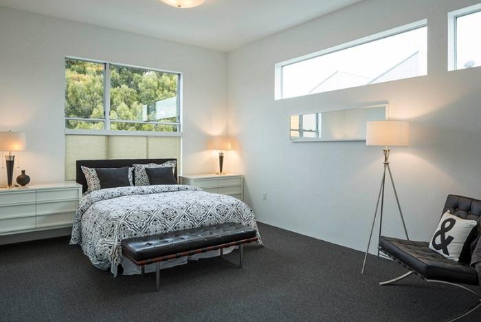 Красивый и сдержанный интерьер спальной в черно-белом цвете с интересным торшером-штативом.
