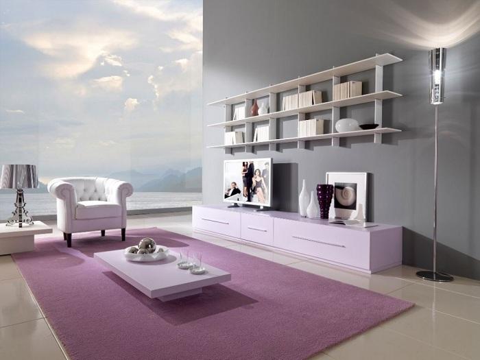 Если оформлять стены гостиной в серо-жемчужные тона, то на пол можно кинуть лавандовый ковер.