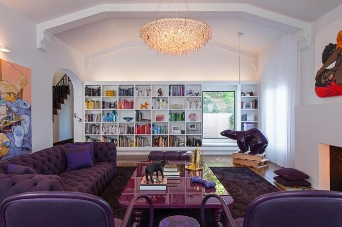 Современная гостиная с темно фиолетовой мягкой мебелью, ковром, столом и светлыми стенами смотрится стильно и красиво.