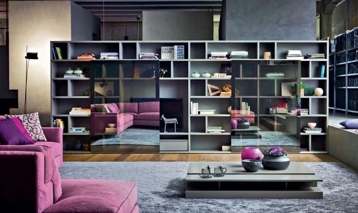 Современная гостиная оформлена в серых тонах с ярким фиолетовым акцентом, за счет чего интерьер смотрится оригинально и красиво.