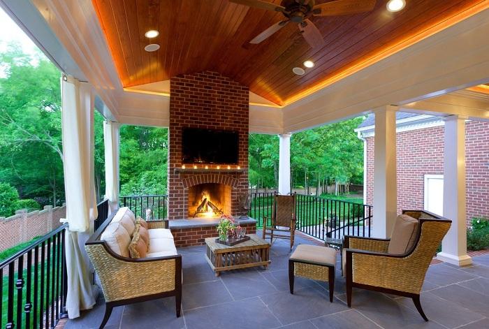 Шикарная терраса загородного дома с теплым скрытым освещением, которое подчеркивает интерьер.