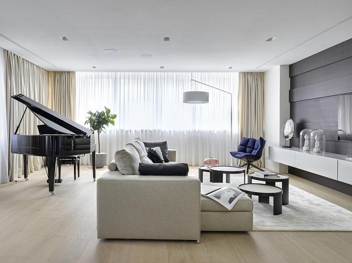 Светлый и опрятный интерьер гостиной с элегантными темными элементами декора.