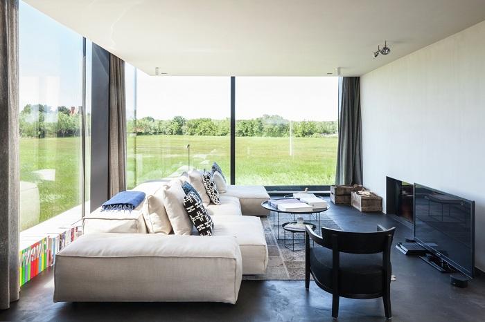 Просторная гостиная с большими окнами обустроена очень комфортно и со вкусом.