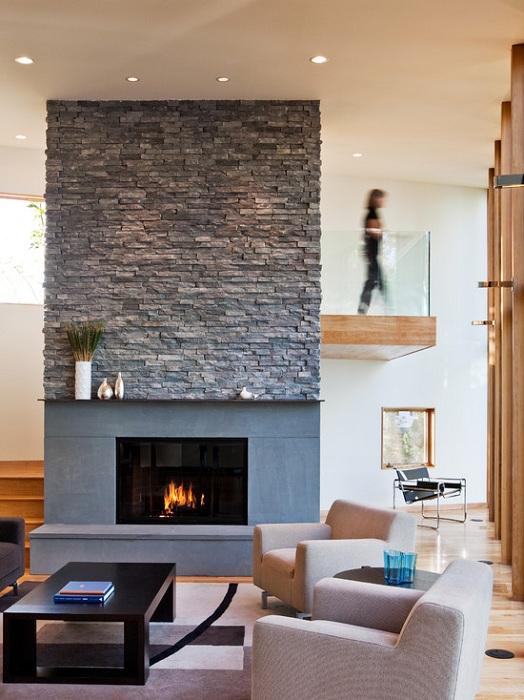 Красивый интерьер гостиной, который преображен благодаря оригинальному камину и каменной стене.