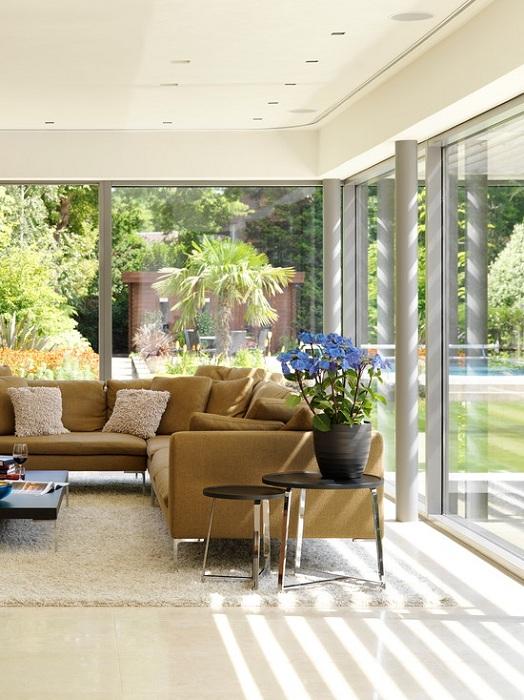 Гостиная в кофейно-сливочных тонах с большими окнами от потолка до пола, что создает ощущение лишнего пространства.