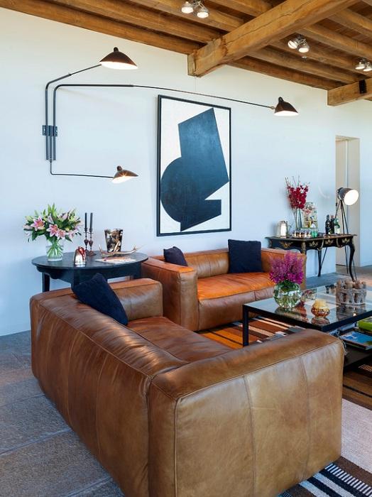 Кожаный диван в сочетании с деревянными планками на потолке, создаст современный интерьер в гостиной.