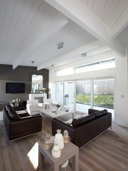 Оригинальный вариант оформления гостиной в мансарде в классических черно-белых тонах.