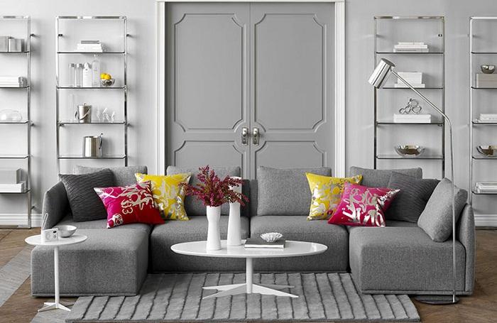 Красивое оформление комнаты благодаря отличному декорированию в серых тонах с добавлением ярких элементов в виде подушек.