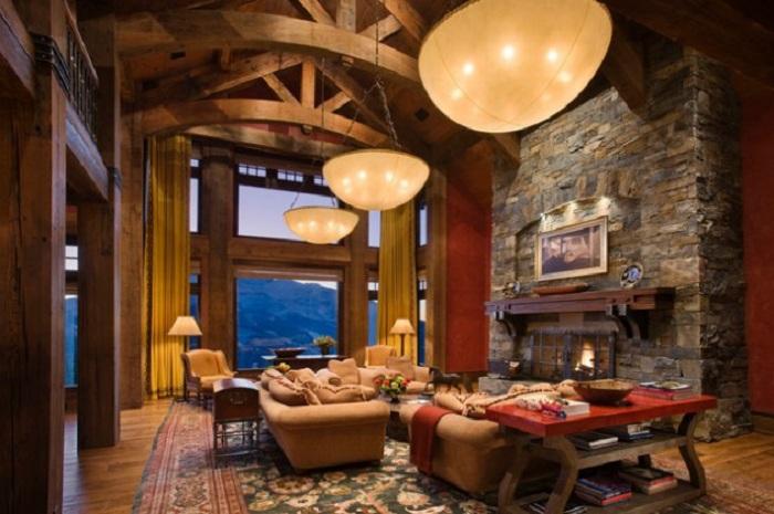 Прекрасная комната с отличным дизайном мебели и камином отделанным декоративным камнем.