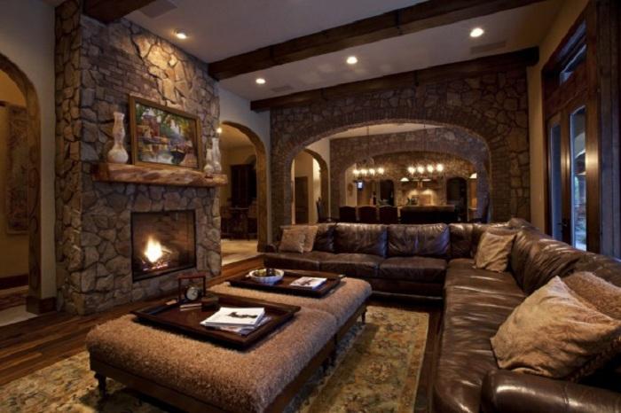 Бежево-коричневая палитра комнаты дополнена уютным камином с декоративного камня.