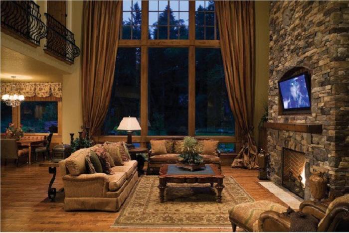 Высокий потолок в гостиной добавляет пространства и красоты комнате, гармонично в которую списывается камин.