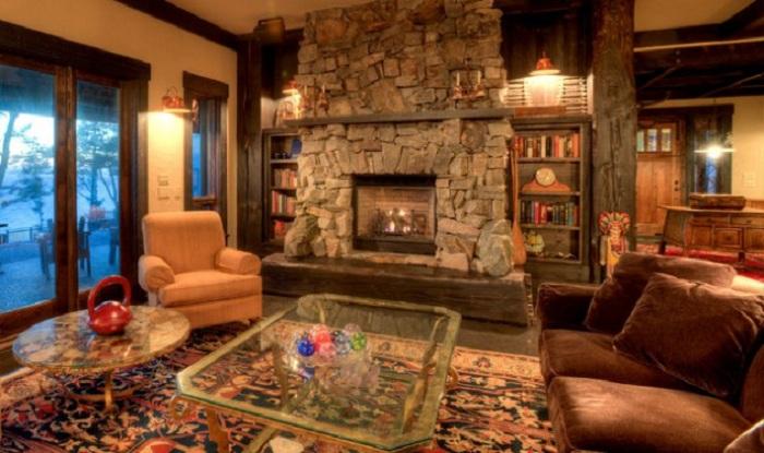 Маленькая уютная комната с интересными элементами интерьера и каменным камином.