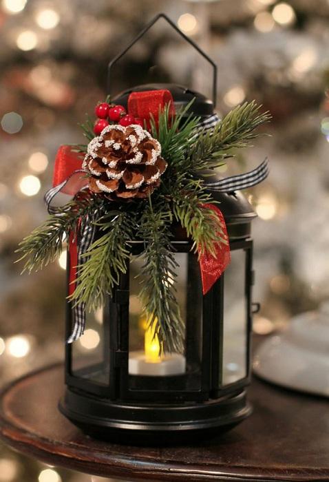 Преобразить фонарь возможно с помощью украшения его ветвями ели и шишкой.