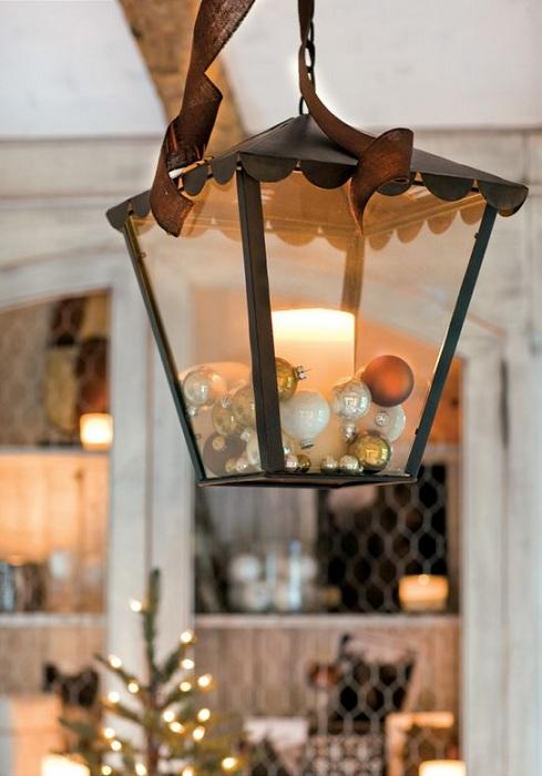 Разместить интересный фонарь с новогодними игрушками для создания праздничного настроения.