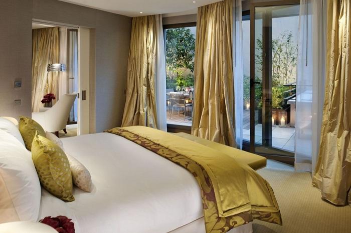 Интересный вариант обустроить интерьер спальной с помощью золотых штор, что понравятся.