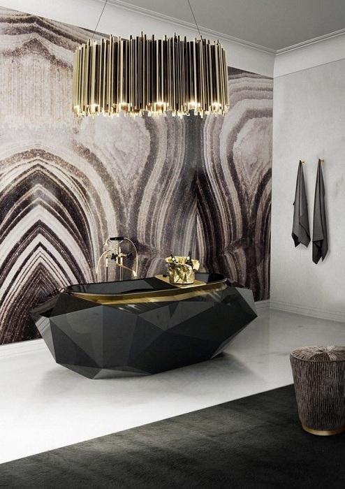 Интерьер в черных тонах с серыми стенами, что украшает золотистая люстра.