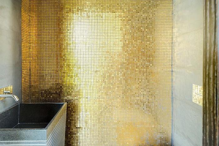 Симпатичная золотая мелкая мозаика станет просто отличным решением при декорировании комнаты такого типа.