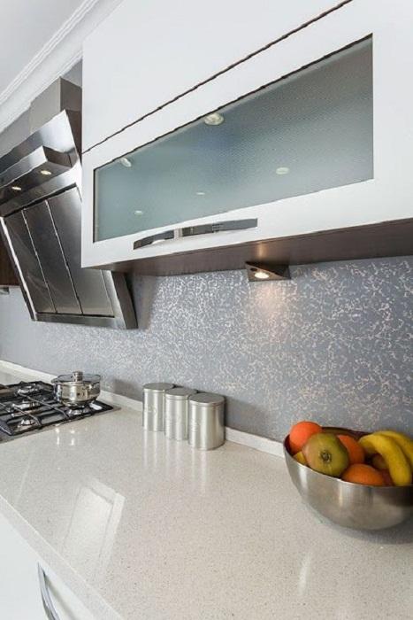 Очень красивый интерьер кухни, рабочая станка которой оформлена очень интересным образом в серовато-голубых тонах.
