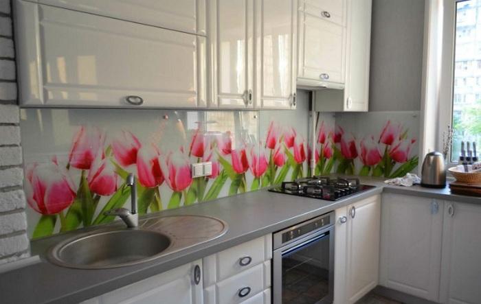 Яркие цветы на фартуке светлой кухни всегда уместны.