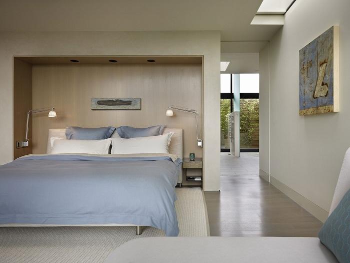 Симпатичная спальня оформлена в бело-голубых тонах, с прекрасной домашней обстановкой и отличными светильниками на стене.