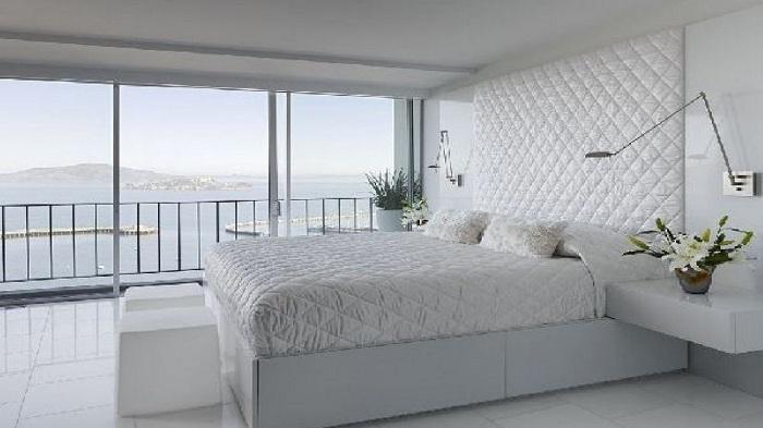 Спальня в белых тонах, с удобными и оригинальными настенными светильниками специально для чтения книг не вставая с постели.