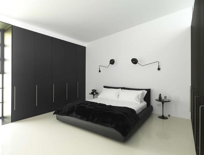 Симпатичное оформление спальни в черно-белых тонах с креативными темными светильниками у изголовья кровати.