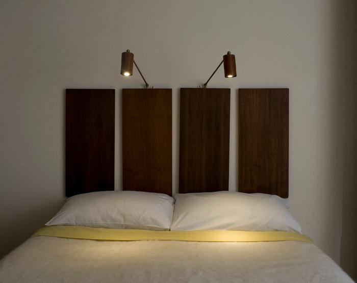 В изголовье кровати весят настенные осветительные приборы в виде бра, дающие рассеянный свет что позволит читать книги прямо в постели.