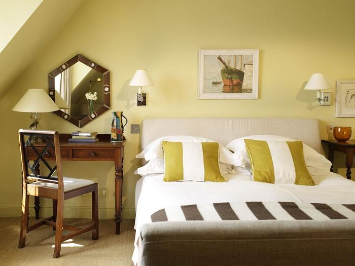 Интересная спальня в красивом оливковом цвете, которая позволяет погрузиться в атмосферу отдыха и безмятежности. Комнату украшают красивые настенные светильники.