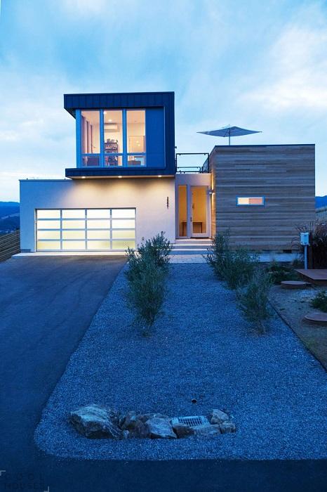 Двухуровневое здание в форме нескольких соединенных между собой прямоугольников возвышается на вершине склона, откуда открывается завораживающий вид на окружающий ландшафт, штат Калифорния, США.