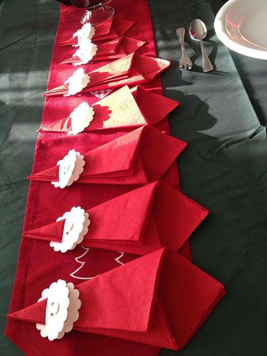 Красивое оформление обеденного алыми салфетками, которые просто, но красиво сложены.