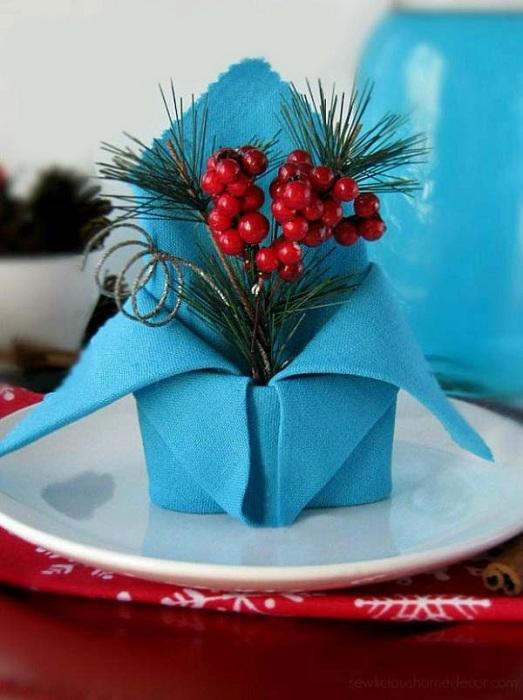Прекрасная голубая салфетка декорированная искусственными ягодами.