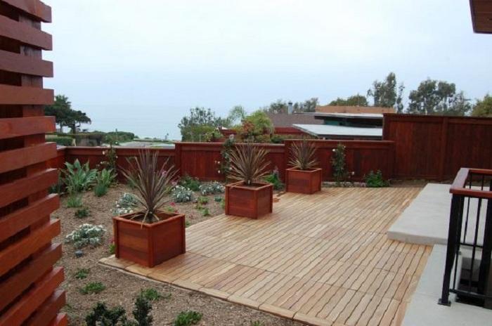 Хороший вариант обустроить территорию около дома при помощи простого варианта декорирования деревянной плиткой.