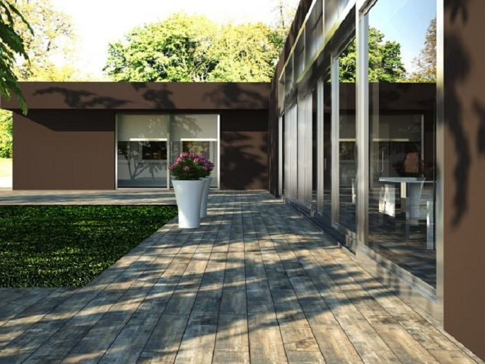 Хороший вариант оформить территорию около дома при помощи деревянной плитки, что заметно преобразит его.