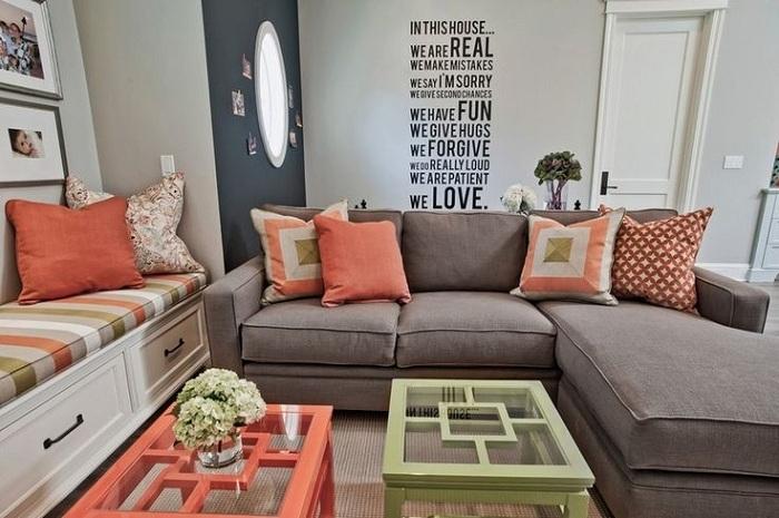 В небольшой квартире, выполненной в светло-серых тонах, добавить настроения помогут небольшие детали и аксессуары, например, персиковые подушки.