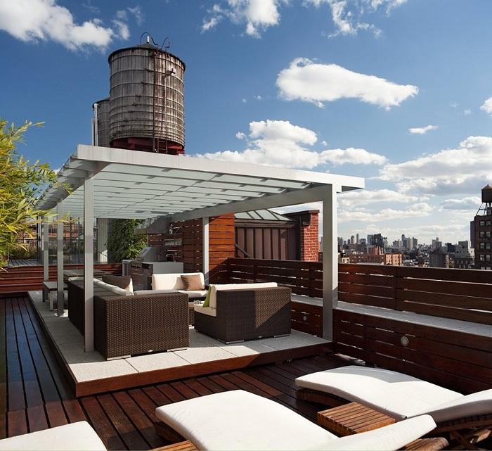Симпатичное оформление места для отдыха на крыше дома под навесом - просто и удобно.