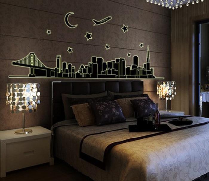 Интерьер спальной в темных тонах с милым изображением светящегося города на стене.