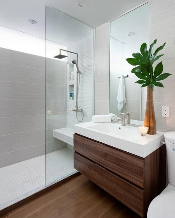 Декор ванной комнаты оформлен в светлых тонах с применением дерева.