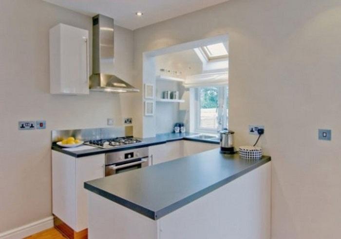 Темно-синяя столешница в сочетании с интересной светлой обстановкой просто и практично вписывается в общий интересный интерьер кухни.