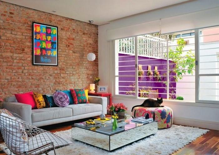 Кирпичная стена создает уютную обстановку в гостиной, а яркие акценты увеличивают площадь.