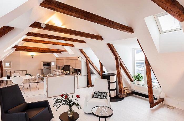 Удачное размещение кухни переходящей в гостиную под чердаком, что добавляет определенного шарма интерьеру.