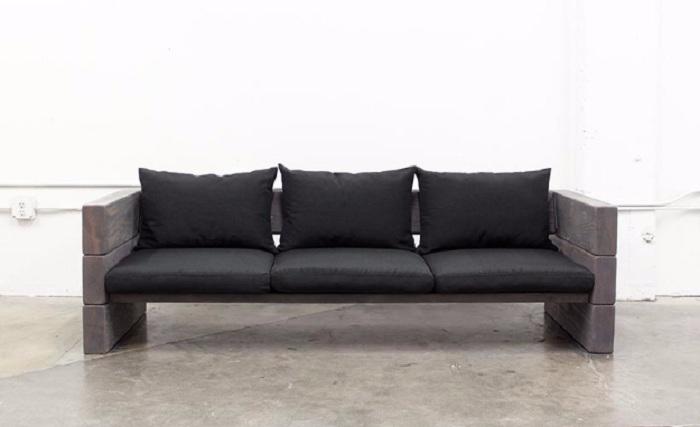 Светлый интерьер комнаты разбавлен черным диванчиком, который выглядит очень оригинально и чудно.