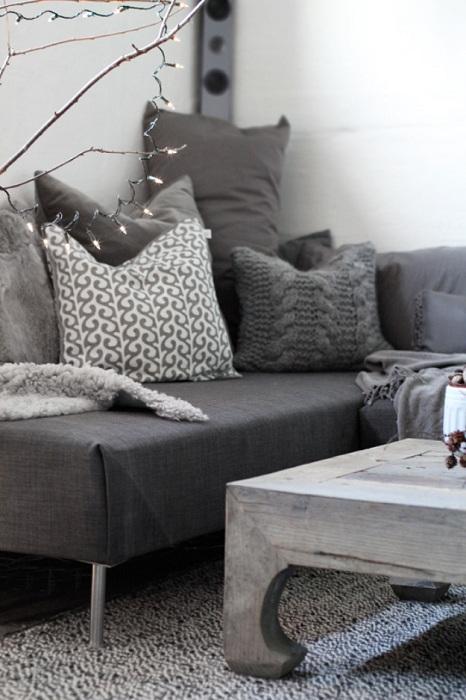 Отличное оформление комнаты при помощи небольшого, но удобного темно-серого дивана.