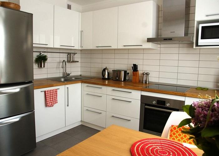 Интерьер кухни в светлых тонах с деревянной столешницей.