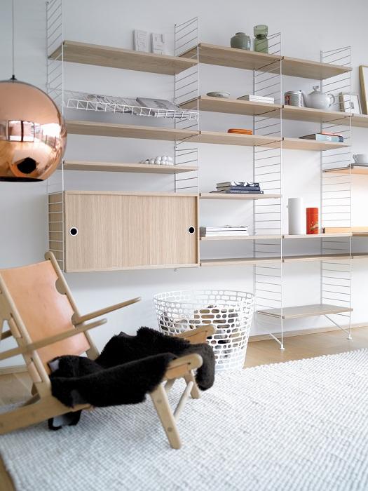 Отличное решение преобразить интерьер комнаты в светлых тонах с интересными настенными полками.