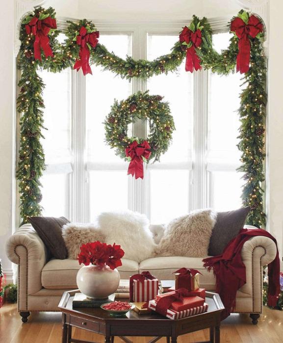 Украсить окно возможно с помощью рождественских веночков.