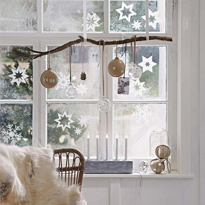 Декорируем окна новогодними игрушками размещенными на ветке.
