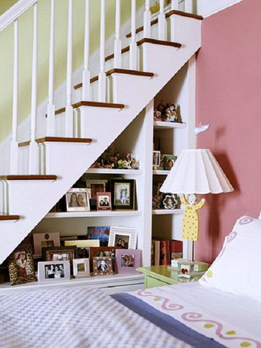 Отличное решение создать крутое оформления пространства под лестницей декорированное при помощи фоторамок, что освежат интерьер.