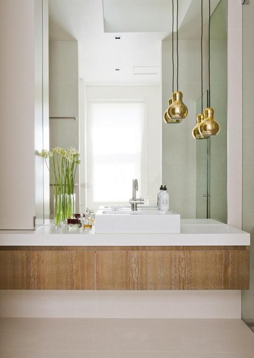 Минималистические особенности этой интересной ванной комнаты дополнены золотыми светильниками, которые свисают с потолка.