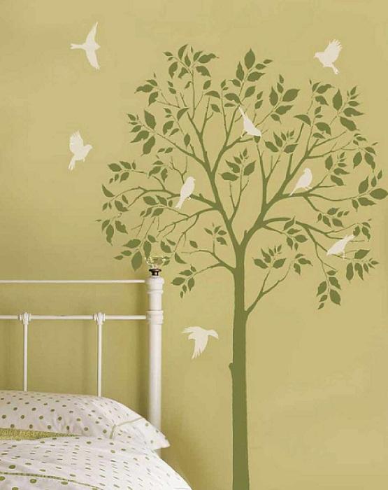 Комната в оливковых тонах с деревом и птицами на стене добавит весеннего настроения даже в самую лютую зиму.