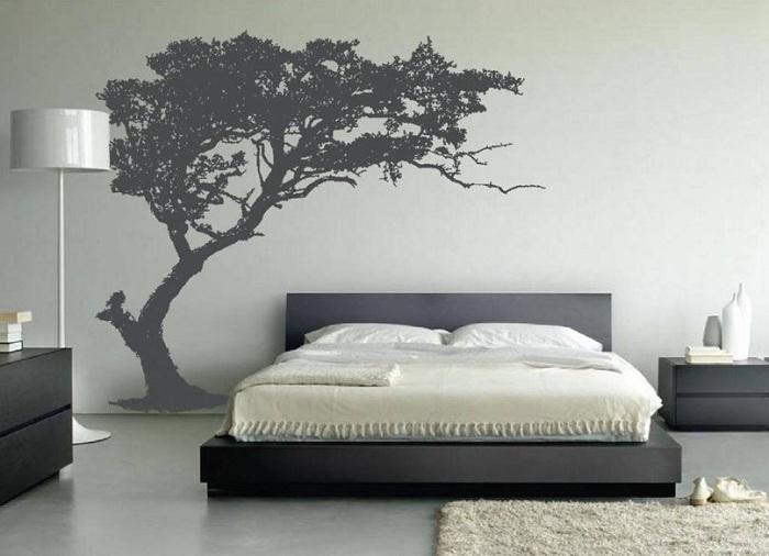 Спальня с шикарным нарисованным деревом на стене создает домашнюю обстановку.